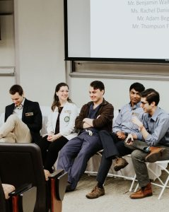 students lead a panel in the front of a classroom